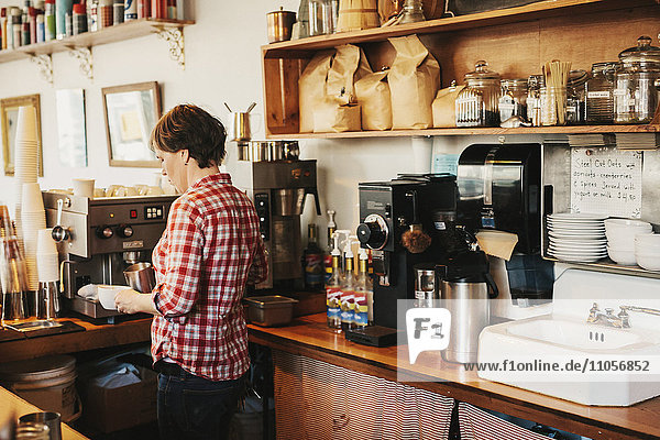 A woman in a plaid shirt working behind the counter in a coffee shop.