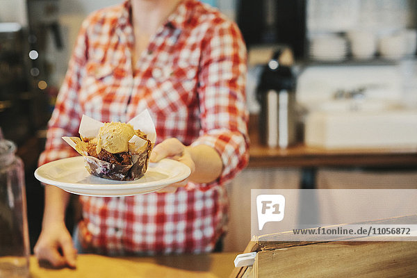 Eine Frau in einem Café  die einen Teller mit einem frischen Muffin mit einer Kugel Eiscreme in der Hand hält. Eine Frau in einem Café, die einen Teller mit einem frischen Muffin mit einer Kugel Eiscreme in der Hand hält.