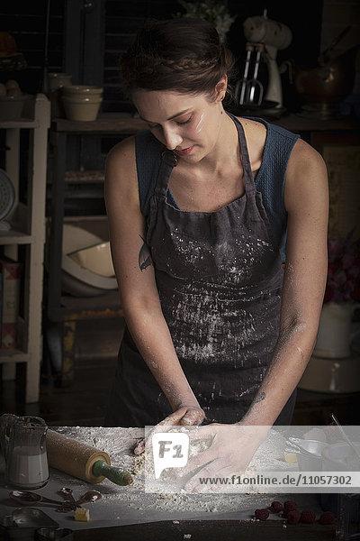 Valentinstag beim Backen  Frau steht in einer Küche und bereitet Teig für Kekse vor.