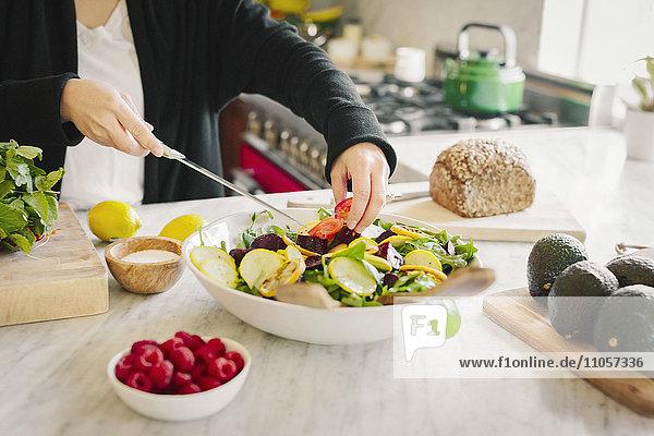 Eine Frau in einer Küche  die ein Salatgericht mit frischem Gemüse zubereitet.