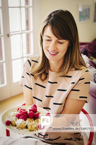 Eine Frau hält einen Teller mit Dessert und eine brennende Kerze. Eine Frau hält einen Teller mit Dessert und eine brennende Kerze.