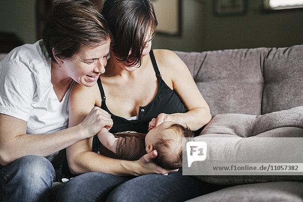 Ein gleichgeschlechtliches Paar  zwei Frauen  die mit ihrem 6 Monate alten Mädchen spielen.