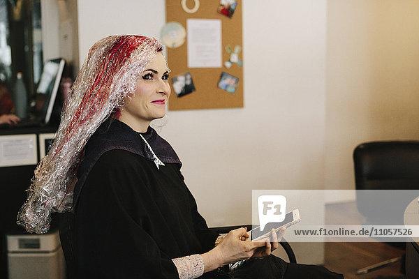 A woman in a hair salon having a hair colour treatment  using a smart phone.