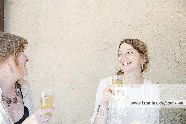 Zwei Frauen sitzen an einem Tisch  lächeln sich an und halten Gläser mit Champagner in der Hand.