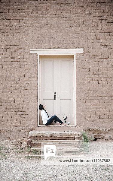 Junge Frau mit langen braunen Haaren  die auf dem Boden vor der Eingangstür eines Gebäudes sitzt. Junge Frau mit langen braunen Haaren, die auf dem Boden vor der Eingangstür eines Gebäudes sitzt.