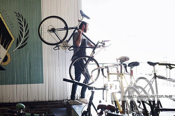 Ein Mann  der in einer Fahrradwerkstatt arbeitet.
