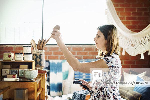 Junge Frau in einem Geschäft,  die einen Holzlöffel in ein Glas legt und einen Strichcode-Scanner hält.