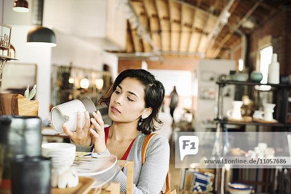 Junge Frau in einem Geschäft  die einen Keramikkrug betrachtet.