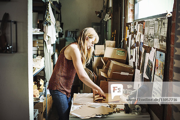 Woman with long blond hair standing in the store room of a shop  wrapping merchandise in brown paper.