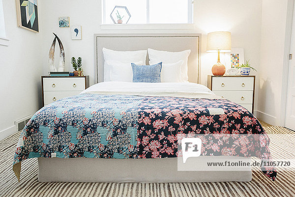 Ein Schlafzimmer in einer Wohnung mit einem Doppelbett  das mit einer geflickten Steppdecke mit Patchwork- und Blumenmustern bezogen ist. Retro-Look.