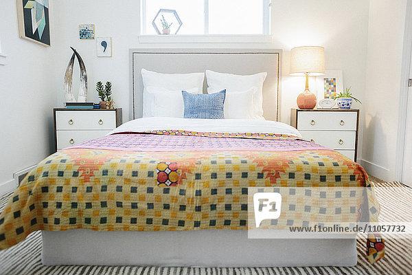 Ein Schlafzimmer in einer Wohnung mit einem Doppelbett und neben Schränken und einer lebhaft geflickten  gemusterten Bettdecke in Orange und Gelb.