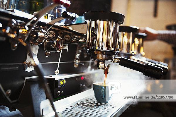 Spezialisiertes Kaffeehaus. Eine Kaffeemaschine  die Kaffee kocht. Dampf und Hitze.