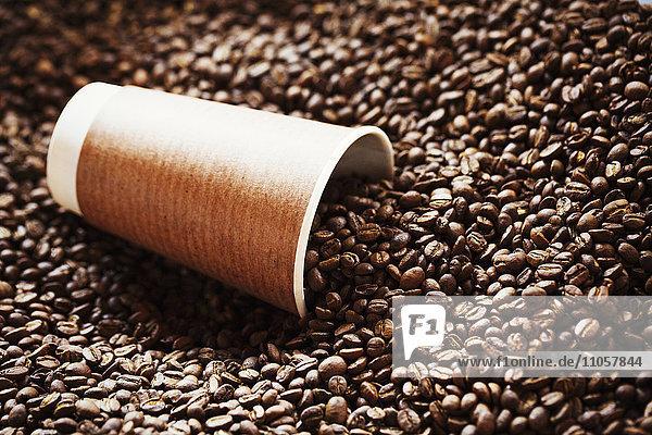 Spezialisiertes Kaffeehaus. Ein Sack geröstete Bohnen und ein Pappbecher.