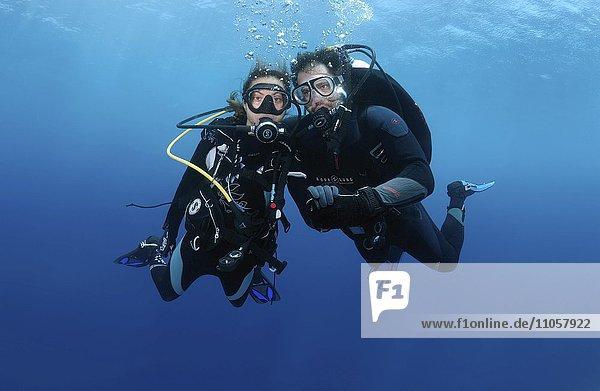 Paar  Taucher im Wasser halten die Hände  Indischer Ozean  Malediven  Asien
