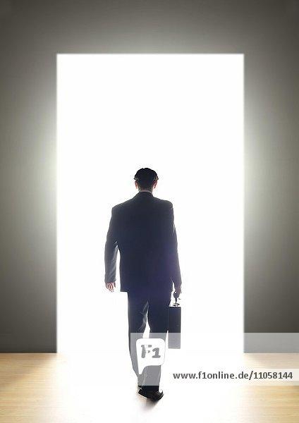 Geschäftsmann geht durch Tür ins Licht  Rückenansicht
