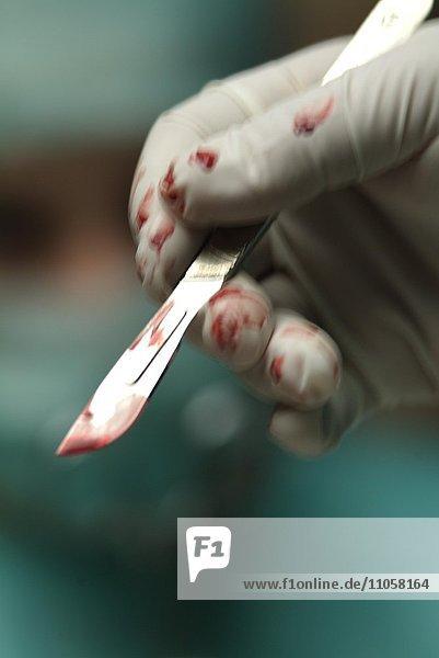 Chirurg  OP-Kleidung  Detail Hand  blutiges Skalpell  Operation