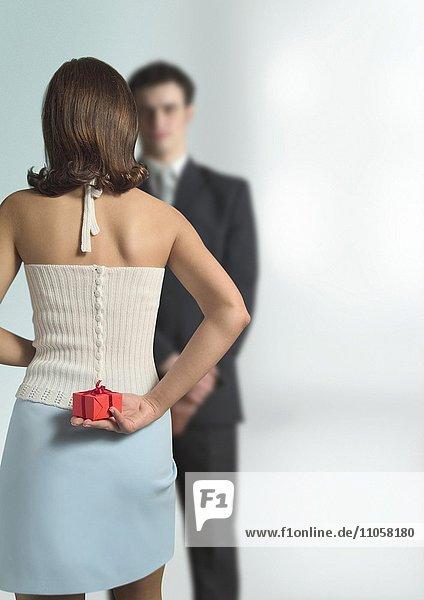 Frau versteckt Geschenk vor ihrem Partner hinter ihrem Rücken