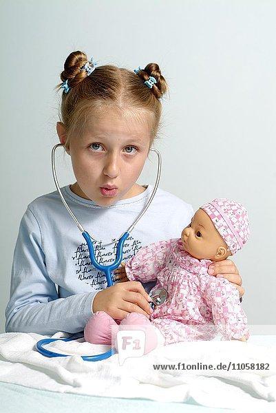 Mädchen hört mit Stethoskop ihre Puppe ab  Symbolbild Berufswunsch Ärztin