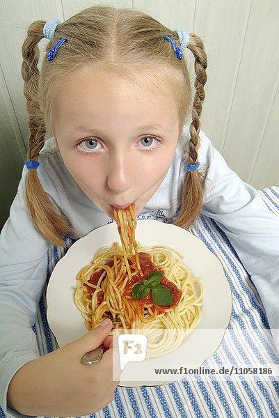 Mädchen isst Spaghetti mit Tomatensauce