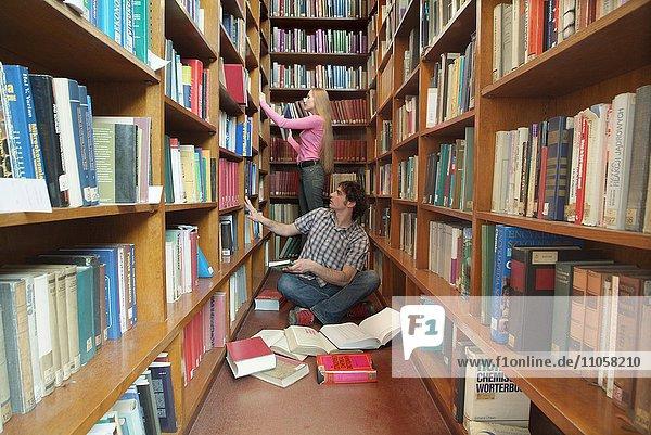 Studenten zwischen Bücherregalen in Universitätsbibliothek
