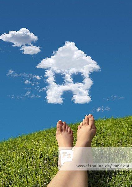 Frau liegt auf Wiese  Detail Füße  Himmel  Wolkenformation in Form von einem Haus