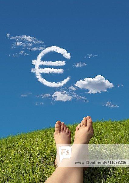 Frau liegt auf Wiese  Detail Füße  Himmel  Wolkenformation in Form von einem Eurozeichen