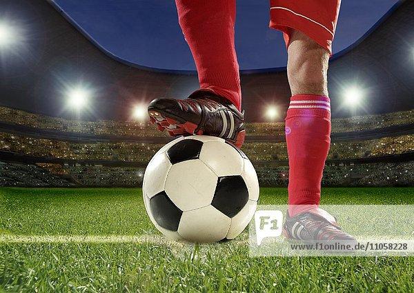 Fußballspieler  Detail Beine  hält Fuß auf Fußball  Fußballstadion