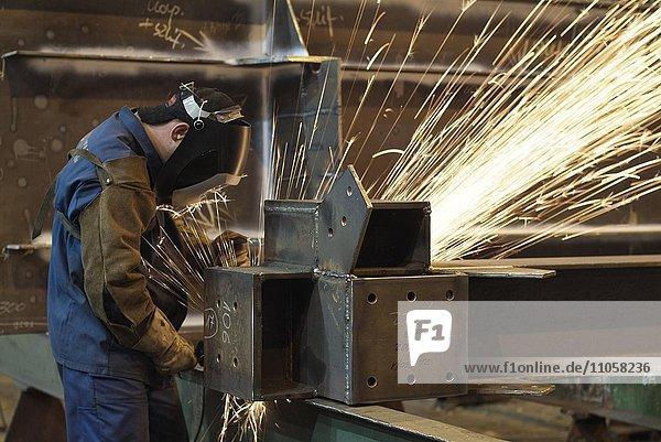 Schweißer mit Schutzanzug im Stahlwerk