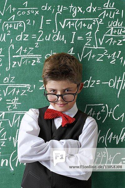Schuljunge mit Brille und Fliege vor Schultafel mit mathematischen Gleichungen