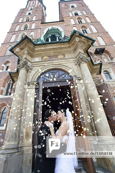 Brautpaar küsst sich  vor der Marienkirche  Krakau  Polen  Europa