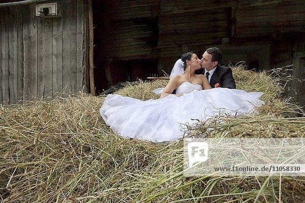 Brautpaar sitzt im Heu  Heustadel