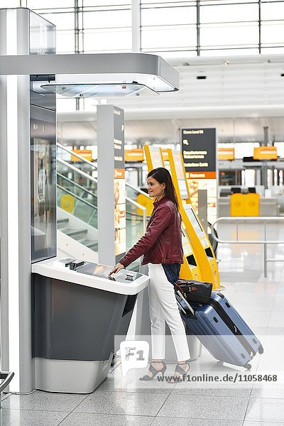 Woman with luggage at the InfoGate  information  Terminal 2  Munich Airport  Munich  Bavaria  Germany  Europe