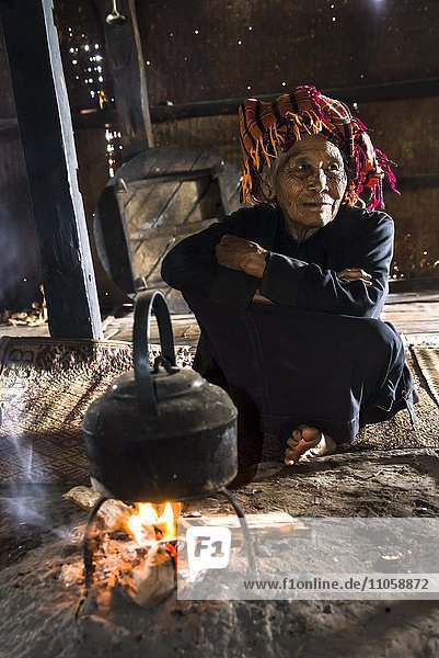 Old woman in the kitchen  kettle on an open fire place in the lodge  mountain tribe or mountain people Pa-O or Pa-Oh or Pao or Black Karen or Taungthu or dew-soo  ethnic minority  near Kalaw  Shan State  Myanmar  Asia