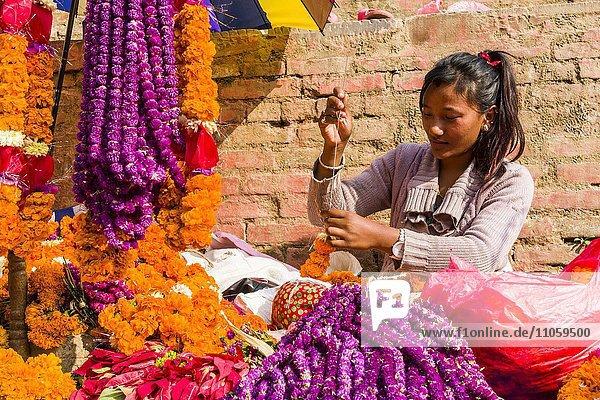 Eine junge Frau arrangiert Blumen auf dem Blumenmarkt am Durbar Square  Kathmandu  Nepal  Asien