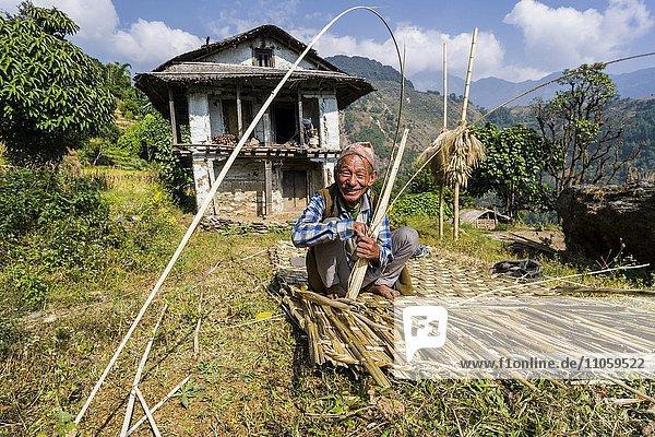 Mann webt einen Bambusmatte als Zaun vor seinem Bauernhaus  Bung  Solo Khumbu  Nepal  Asien