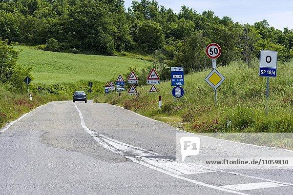 Straße flankiert von vielen Verkehrszeichen  Castiglione d'Orcia  Val d'Orcia  Toskana  Italien  Europa