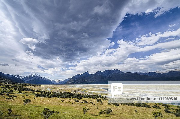 Grassland in front of the wide riverbed of the Tasman River  dramatic clouds  Mount Cook National Park  Pukaki  Canterbury Region  New Zealand  Oceania