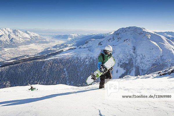 Snowboardfahrer beim Aufstieg mit Blick auf Innsbruck und Inntal  Axamer Lizum  Tirol  Österreich  Europa
