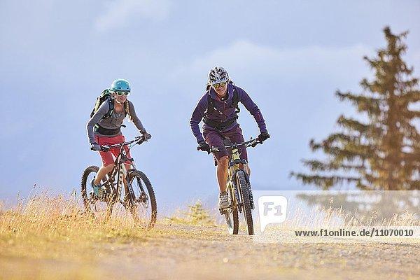 Zwei Mountainbiker mit Helm fahren auf einem Schotterweg  Mutterer Alm bei Innsbruck  Tirol  Österreich  Europa