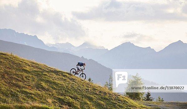 Mountainbiker bei der Abfahrt über einen Forstweg  Mutterer Alm bei Innsbruck  hinten Nordkette der Alpen  Tirol  Österreich  Europa Mountainbiker bei der Abfahrt über einen Forstweg, Mutterer Alm bei Innsbruck, hinten Nordkette der Alpen, Tirol, Österreich, Europa