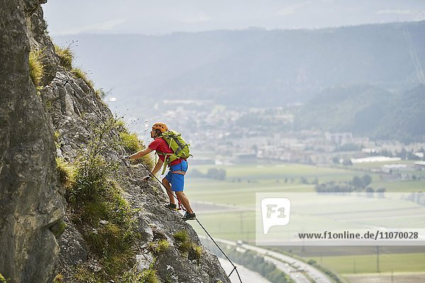 Bergsteiger  Kletterer mit orangen Helm beim Aufstieg am Klettersteig  Zirl  Innsbruck  Tirol  Österreich  Europa