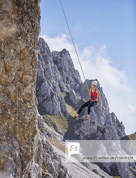 Kletterin mit Helm schwingt im Kletterseil an Felswand  Nordalpen  bei Innsbruck  Tirol  Österreich  Europa