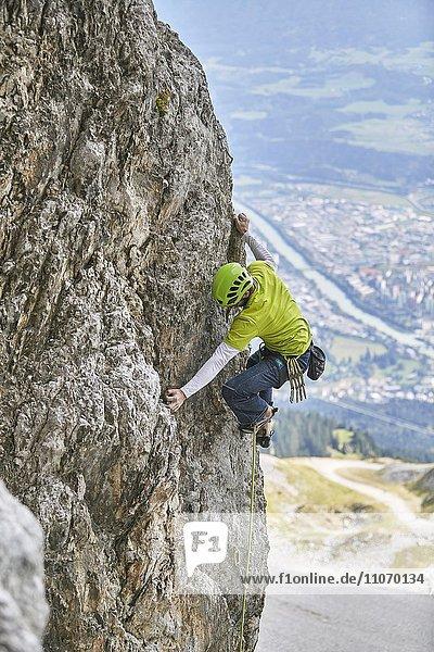 Kletterer mit Helm klettert an einer Felswand  hinten Innsbruck  Nordalpen  Tirol  Österreich  Europa