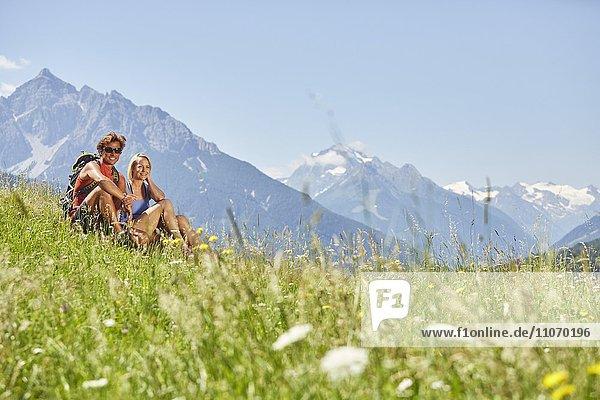 Mann und Frau sitzen in der Wiese  Berge dahinter  von links Serles und Habicht und Stubaier Gletscher  Patsch  Rosengarten  Innsbruck  Österreich  Europa