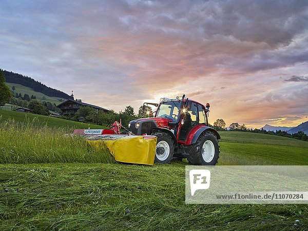 Traktor mäht bei Sonnenaufgang ein Feld  Hopfgarten  Brixental  Tirol  Österreich  Europa