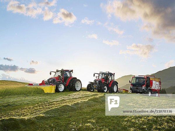 Drei Fahrzeuge  zwei Traktoren und ein Transporter mähen Wiese  Hopfgarten  Brixental  Tirol  Österreich  Europa