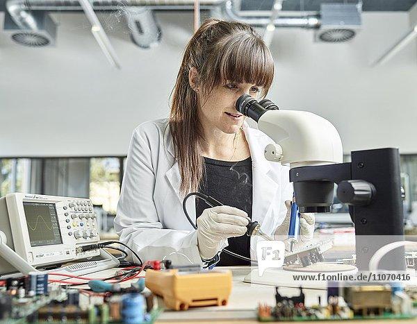 Technikerin  Frau 20-25 Jahre  mit weißem Laborkittel lötet eine Platine in einem Elektronik Labor  Wattens  Innsbrucker Land  Tirol  Österreich  Europa