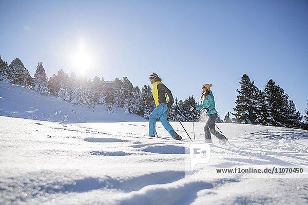 Frau und Mann  Paar wandert mit Schneeschuhen in verschneiter Landschaft  Gegenlicht  Patscherkofel  Patsch  Innsbruck  Tirol  Österreich  Europa