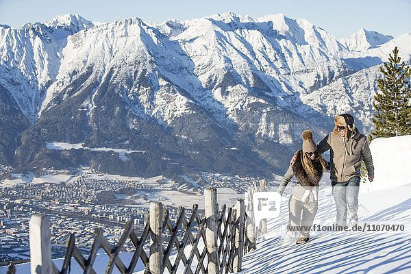 Frau und Mann wandern im Schnee mit Bergkulisse  Nordkette  Patscherkofel  Patsch  Innsbruck  Tirol  Österreich  Europa