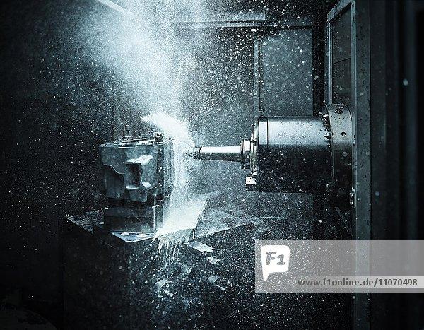 Metallverarbeitung CNC Maschine  CNC Fräse bohrt und fräst in einen Zylinderkopf  Bohrer wird mit Kühlflüssigkeit geschmiert und gekühlt